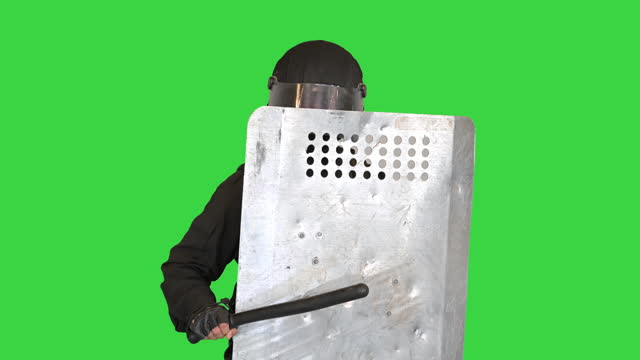 Riot Police unit holding position covering with a shield and holding a baton on a Green Screen, Chroma Key