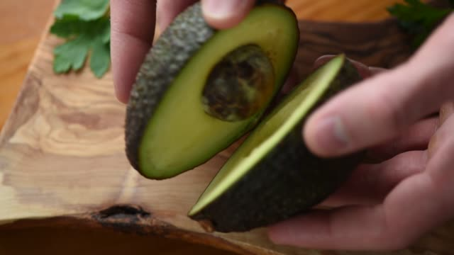 Ripe Avocado In Hands Hands holding ripe avocado in hands. Avocado open. Ripe tasty avocado, vegan healthy food avocado stock videos & royalty-free footage
