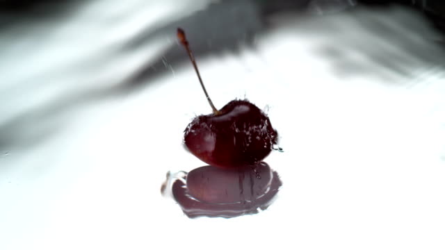 Ripe cherry falling into water. Super slow motion