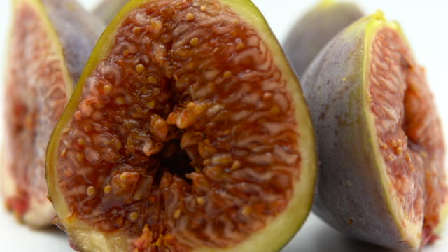 Ripe fresh figs in shape of heart cut in half on white background. Exotic food isolated, purple fruit full of vitamins. Healthy nutrition and antioxidant concept