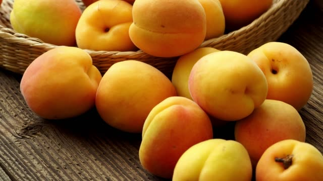 ripe juicy apricots in a basket on a wooden background - albicocca video stock e b–roll