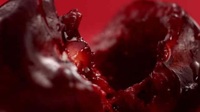 Ripe, juicy cherry split in half. Extreme close up Cherry flesh close up. Ripe fruit on red background cherry stock videos & royalty-free footage