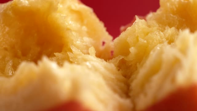 Ripe, juicy peach split in half. Extreme close up Peach flesh close up. Ripe fruit on red background peach stock videos & royalty-free footage