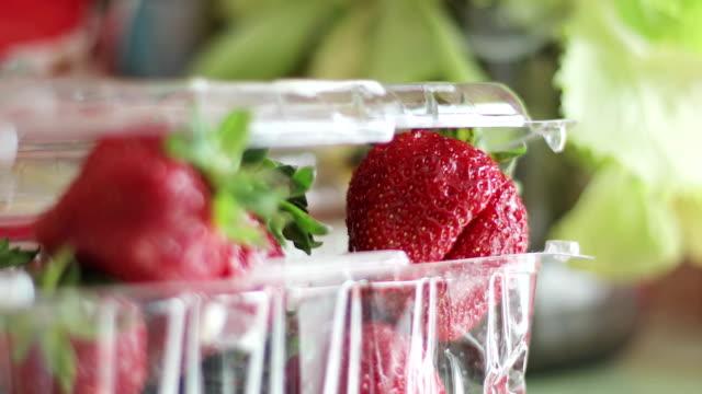 ripe juicy strawberries in a plastic transparent box. - bacca video stock e b–roll
