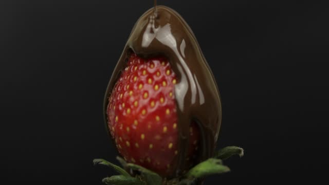 ripe juicy strawberry are poured over chocolate on a dark background. close up - сироп стоковые видео и кадры b-roll