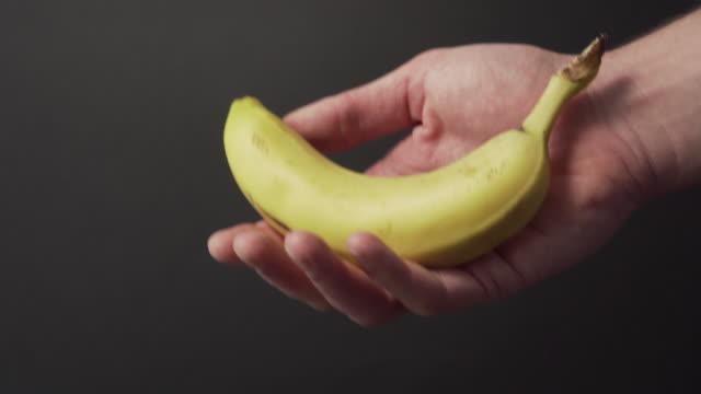 vídeos de stock, filmes e b-roll de banana suculenta madura balança na mão de um jovem close-up em um fundo escuro - descascado