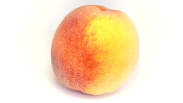 Ripe  peach fruit rotating on white video