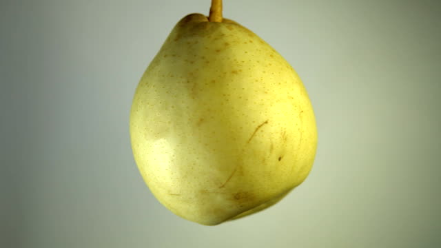 Ripe pear rotates against a light background Ripe yellow pear rotates against a light background, closeup view shot with seamless looping. pear stock videos & royalty-free footage