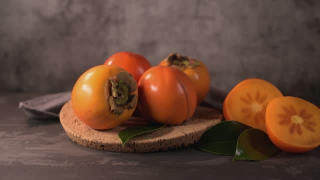 vídeos de stock e filmes b-roll de ripe persimmon fruits in a cork plate - diospiro