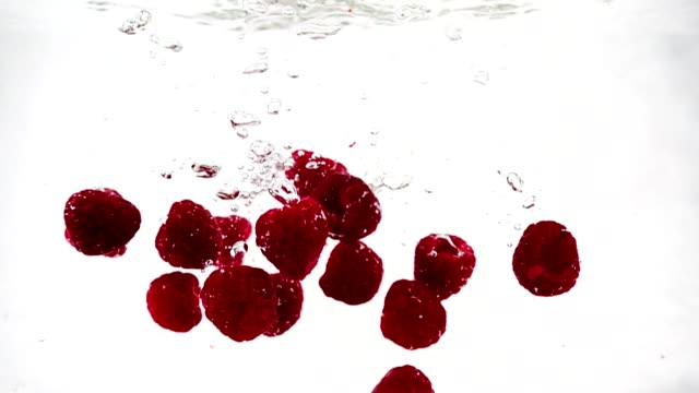 vídeos de stock e filmes b-roll de a ripe raspberry falls into the water with a lot of small bubbles. video of berry on isolated white background - framboesa