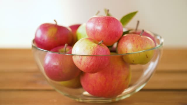 vídeos de stock e filmes b-roll de ripe red apples glass bowl on wooden table - saladeira