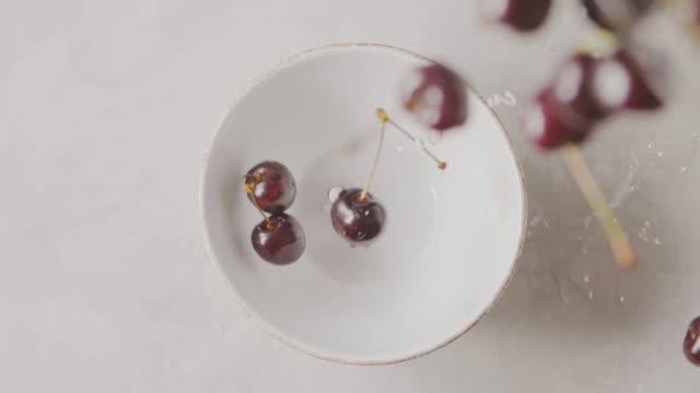 vídeos y material grabado en eventos de stock de las cerezas rojas maduras con gotas de agua caen en un recipiente de cerámica blanca de un recipiente de vidrio sobre una mesa blanca. vista superior. enfoque suave. cámara lenta. vídeo full hd, 240fps, 1080p - cuenco