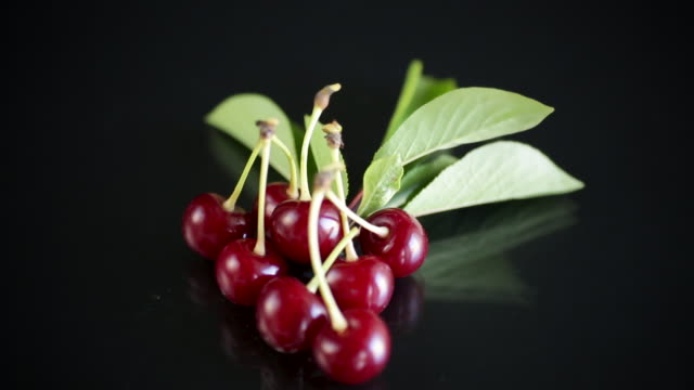 ripe red natural cherry on a black video