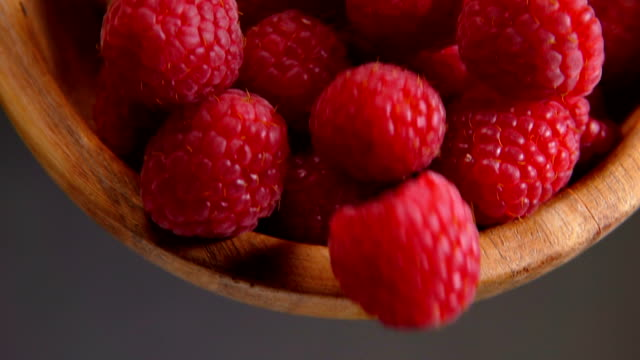 Ripe red raspberries are poured from a bamboo bowl