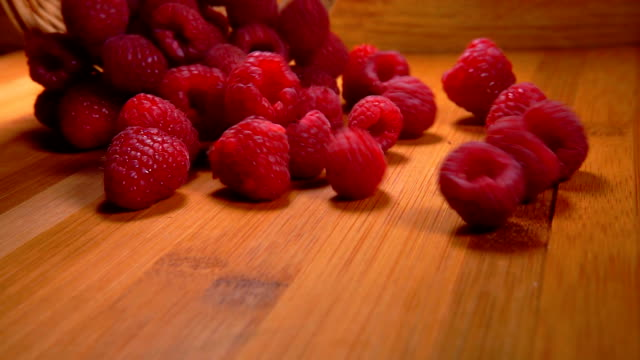 ripe red raspberries are poured from a wicker basket - bacca video stock e b–roll