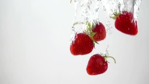 vidéos et rushes de fraises mûres tombant par l'eau - fraise