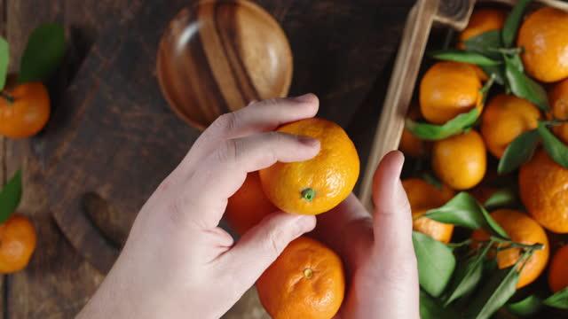 Ripe tangerines in the hands of men.