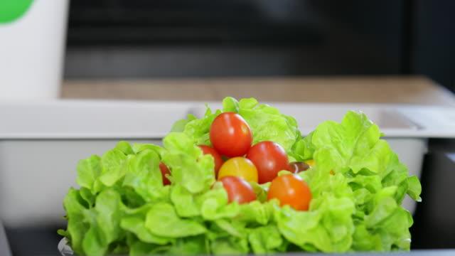 Ripe tomato falling on lettuce in bowl