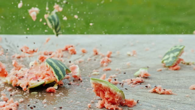 A ripe watermelon falls to the floor and smashes to pieces. Sprays fly in all directions. Slow motion 180 fps video video