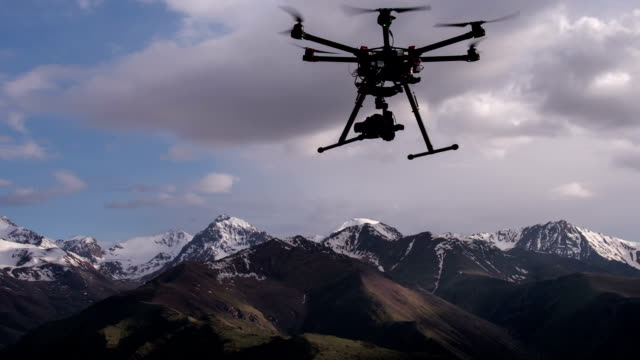 Rise Copter in the Air Radio controlled hexacopter rises into the air from the ground position on the background of snowy mountains telephone receiver stock videos & royalty-free footage