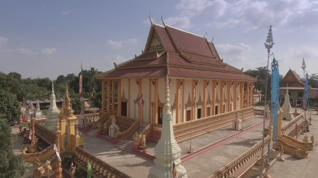 rise up drone shot of a traditional buddhism pagoda with green landscape in the background - cambogia video stock e b–roll