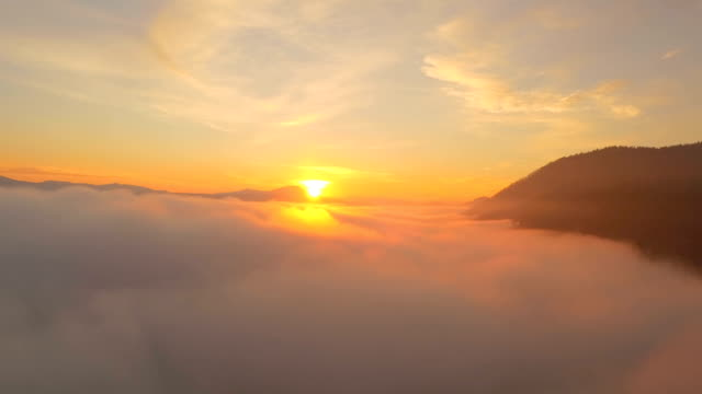 AERIAL: Rising above the tick fog and revealing golden sunrise sun AERIAL: Rising above the tick fog and revealing golden sunrise sun horizon over land stock videos & royalty-free footage