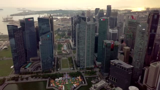 Rising aerial footage of Marina Bay Financial Centre and carnival amusement park with PSA at background.