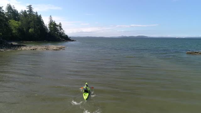 Rising Aerial of Man Paddling Kayak Out to Sea Slow Motion video