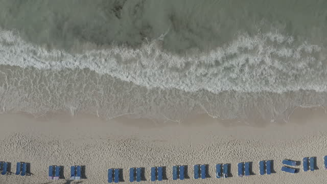 Rising drone shot over breaking waves in the surf on tropical beach with deckchairs video
