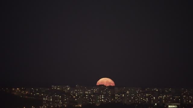 rising full super moon über nacht stadt. - slowakei stock-videos und b-roll-filmmaterial