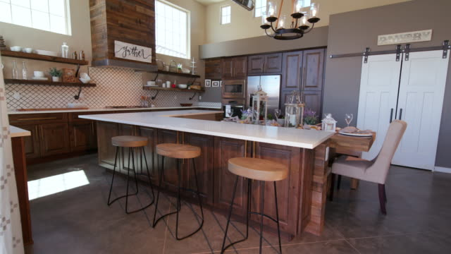 rising on modern kitchen island with stools - kitchen situations video stock e b–roll