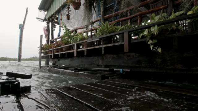 Rising sea levels flooding traditional stilt house on Andaman sea coastline Thailand