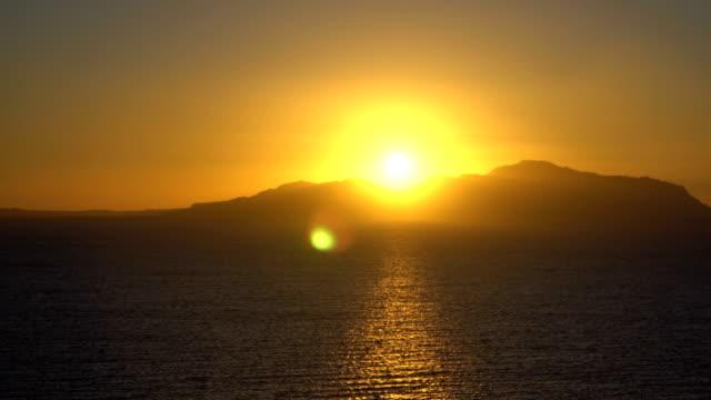 rising sun over the sea and desert mountains - линия экватора стоковые видео и кадры b-roll