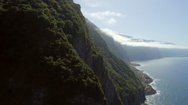 vídeos de stock e filmes b-roll de rising view of mountainous coastline of madeira - ilha da madeira
