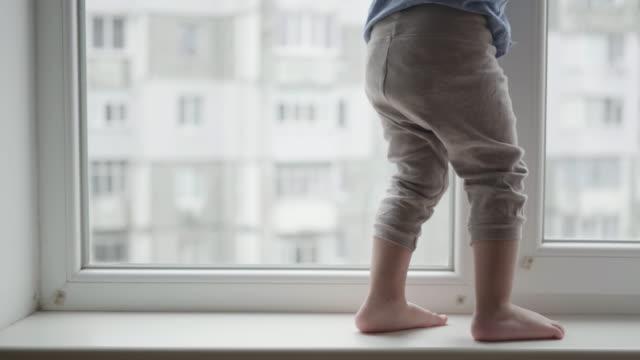 vídeos de stock, filmes e b-roll de risco à vida, os pés das crianças andam no windowsill, um menino pequeno no perigo perto da janela - objeto manufaturado