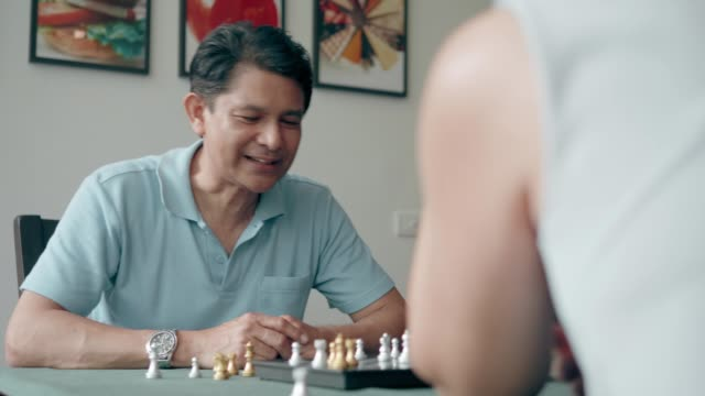 vídeos de stock e filmes b-roll de rivalry chess: senior couple trying to play chess for relaxation at home - active brain
