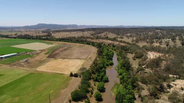 HV river back from farms Narrow stream of Hunter river in Hunter valley during drought – aerial flying over agriculture fields, cultivated farms and dry outback plains. paddock stock videos & royalty-free footage