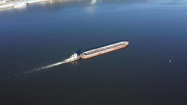 牽引中の川のはしけは川の水路に沿って浮かぶ - ドローン空中軌道ショット - はしけ点の映像素材/bロール