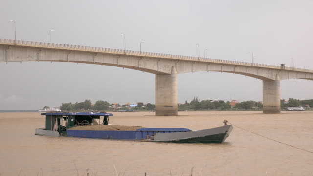 river barge loaded with dredged sand tied to shore nearby a bridge video