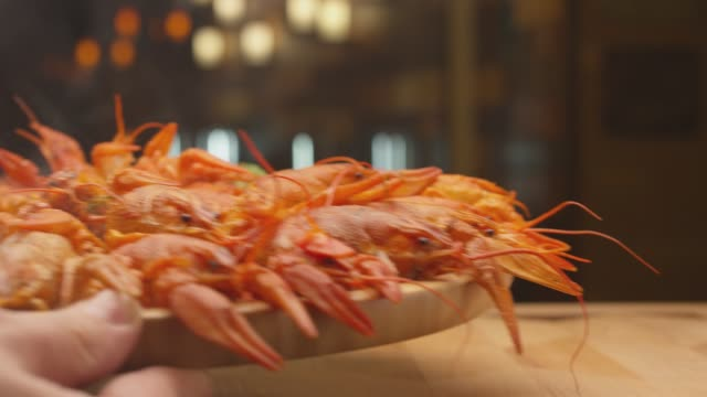 river boiled crayfish a good snack to beer. waiter puts on the table a plate of boiled red river cancer . a plate of  fuming or smoking hot crawfish in the restaurant. shot on red camera slow motion. - granchio video stock e b–roll