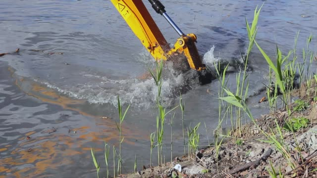River, canal is being dredged by excavator