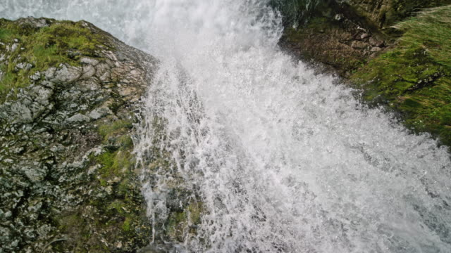 Video SLO MO River caught in a rocky river bed flowing over the rocks creating a beautiful waterfall