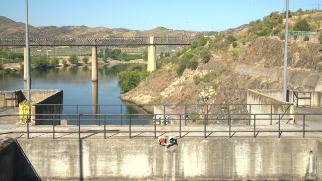 vídeos de stock e filmes b-roll de river cruise boat slowly enters the lock of the pocinho dam on the river douro in portugal - vídeos de barragem portugal