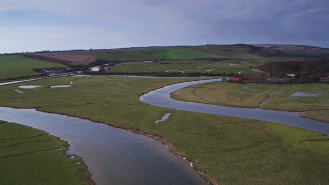 river cuckmere winding through farmland in east sussex - drone shot - south downs video stock e b–roll