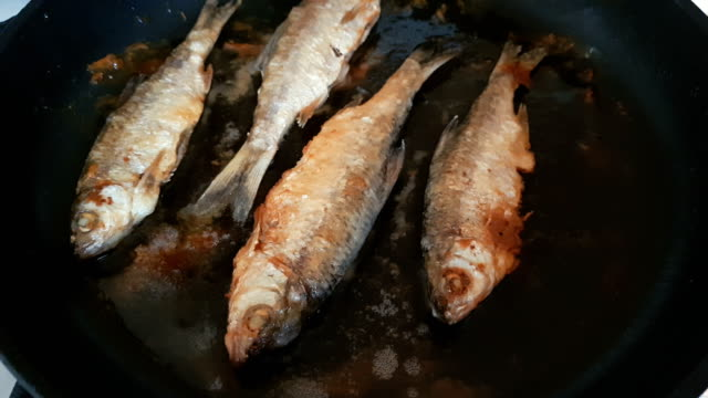 River fish frying on pan close up, dynamic scene, toned video. Delicious fresh food in the process of cooking. video