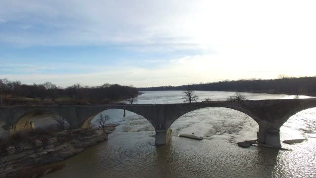 River flowing past abandoned bridge that is falling apart video