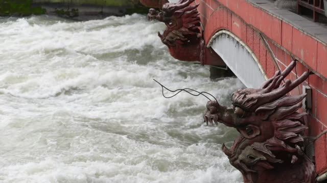 River flowing under a bridge with red dragon head sculptures video