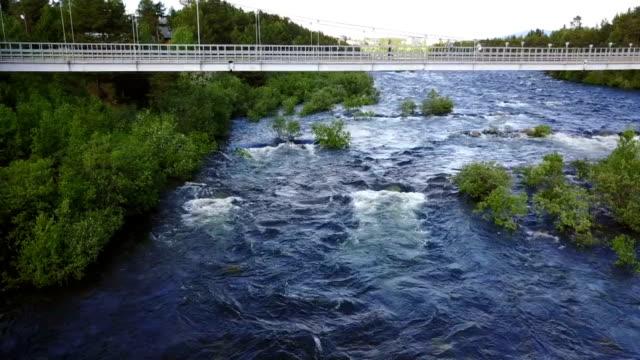 vídeos de stock e filmes b-roll de river niva and footbridge through it - multicóptero