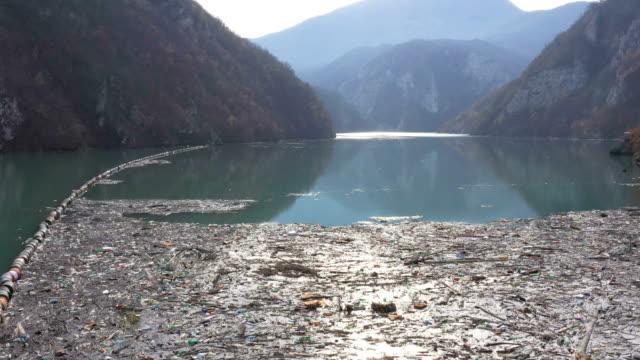fluss mit müll verschmutzt - umweltverschmutzung stock-videos und b-roll-filmmaterial