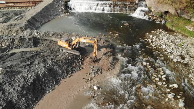 River site construction - building a dam Excavator digging a pit, changing the river bed natural path. Drone shoot of an excavator at construction site of a dam. crane construction machinery stock videos & royalty-free footage